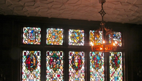 Stained glass windows depicting scenes from five Shakespearean plays.
